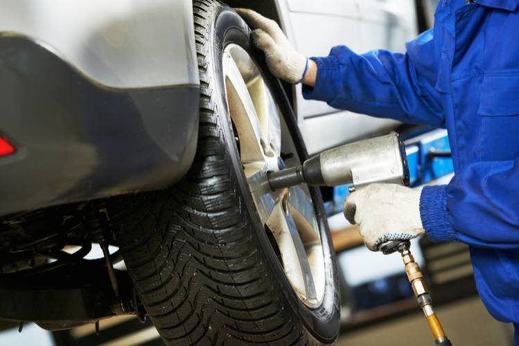 auto mechanic fitting car tyres